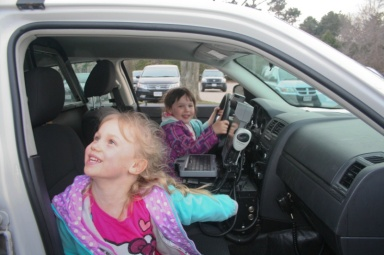 Siobhan and Chloe pretend to take the parked cruiser for a spin