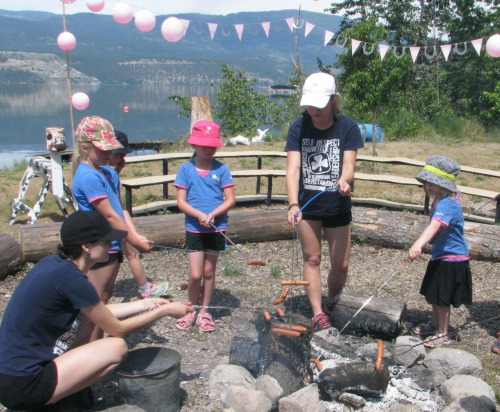 Girls cooking at campfire